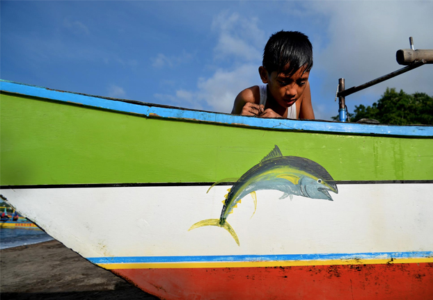A little boy admires his family boat's sigil - a jumping Bankulis or Yellowfin Tuna. The boy's future might very well depend on whether these oceanic giants keep on jumping.  PHOTO COURTESY OF WWF-PHILIPPINES